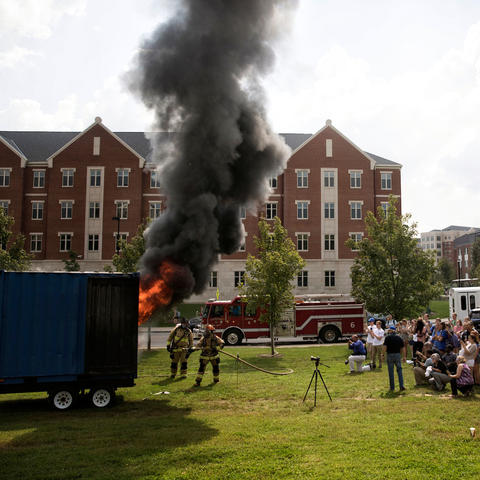 photo of people watching fire demonstration of how quickly a residence hall room can catch fire