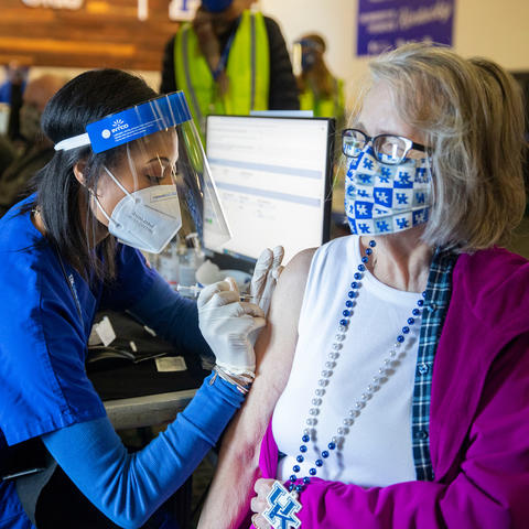 A lady wearing a UK mask and necklace receives a covid shot from a Health Sciences student