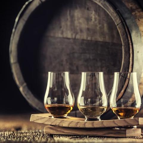 Glasses of whisky in front of barrel