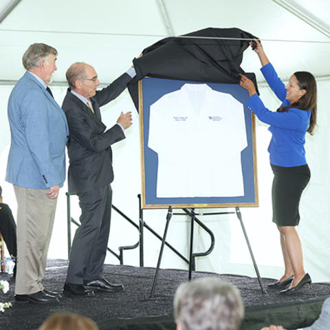 photo of Dr. Capilouto and Dr. Wendy Jackson unveiling medical coat for Dr. Michael D. Rankin