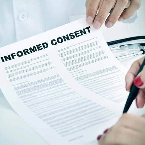 A woman signs an informed consent document