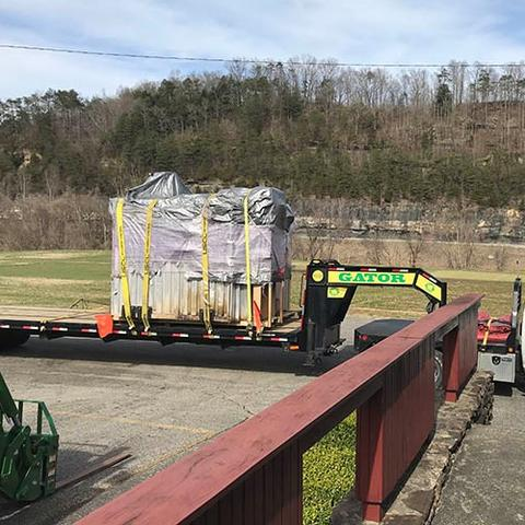 Image of truck hauling trailer with kiln wrapped up