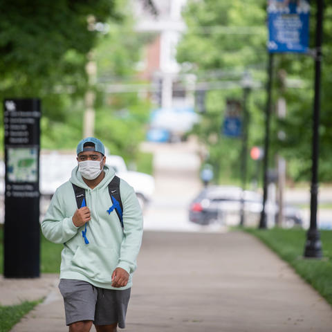 male student walking on campus wearing mask