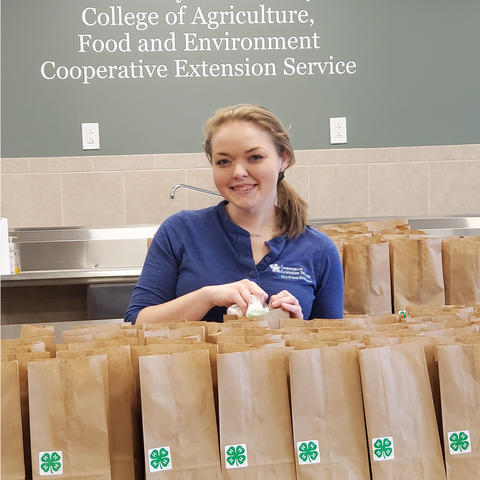 Melissa Schenck poses with brown bags