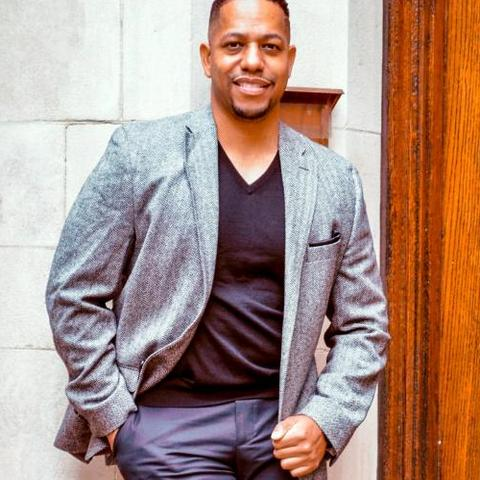 Quentin Tyler pictured in grey jacket against stone background