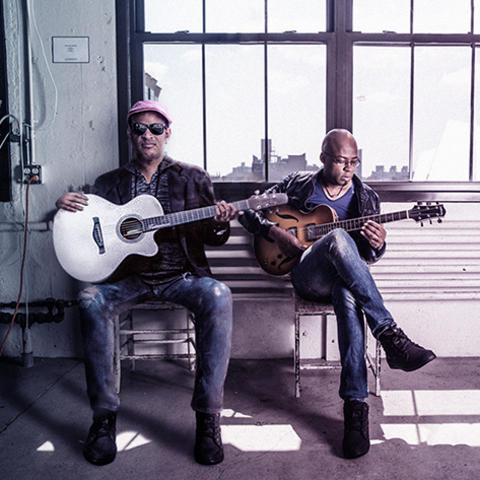photo of Raul Midon and Lionel Lueke with their guitars seated on bench
