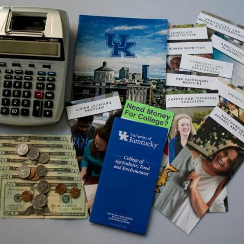 Image of calculator, dollar bills and pamphlets regarding scholarships and the College of Agriculture, Food and Environment