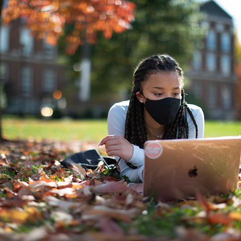 female student wearing mask lying in fallen leaves looking at her computer in front of the Main Building.
