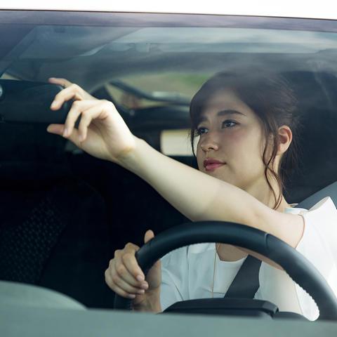 Woman adjusting her car mirror.