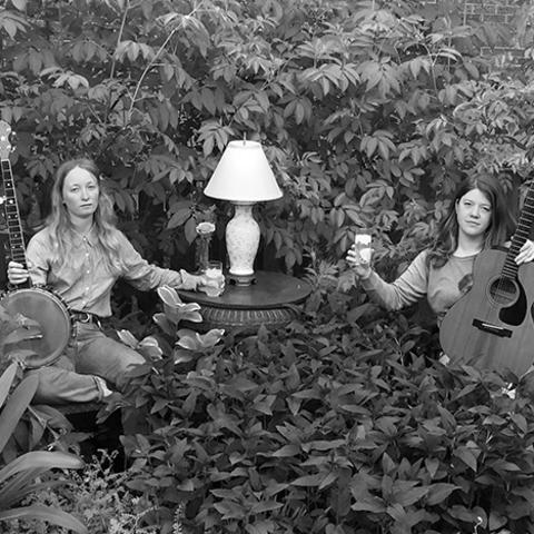black and white photo of the duo The Other Years seated with banjo and guitar by side table with lamp in overgrown field