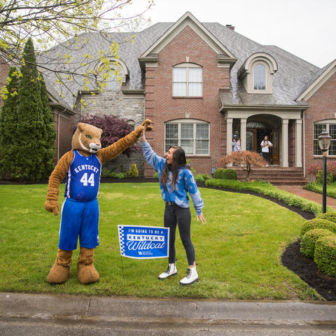 "Wildcat high fives with incoming freshman in her front yard with yard sign saying ""I'm going to be a Kentucky Wildcat"""